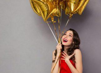 Frau im roten Kleid mit goldenen Luftballons