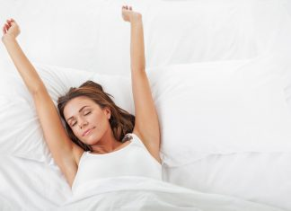 Frau streckt sich im Bett