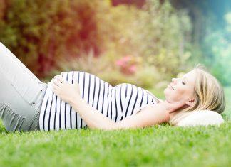 Schwangere liegt auf einer Wiese