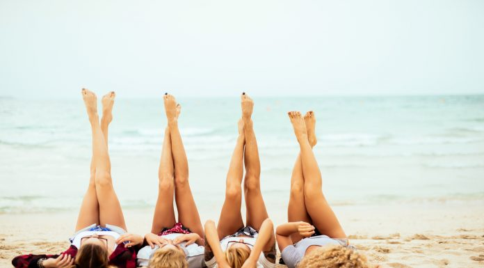 Vier Frauen strecken am Strand ihre schönen Beine in die Luft