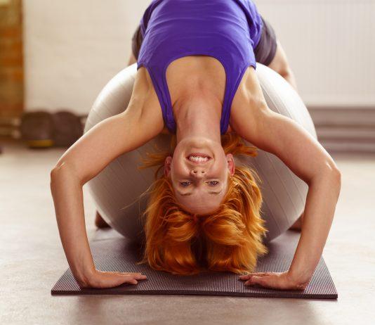 Frau trainiert ihren Rücken auf Gymnastikball