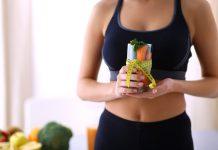 Frau hält ein mit Gemüse gefülltes Glas mit Massband in der Hand