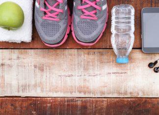 Sport Schuhe und Wasserflasche auf Holzboden als Vorbereitung zur Workout Strategie