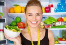 Lächelnde junge Frau mit frischem Gemüse vor Kühlschrank