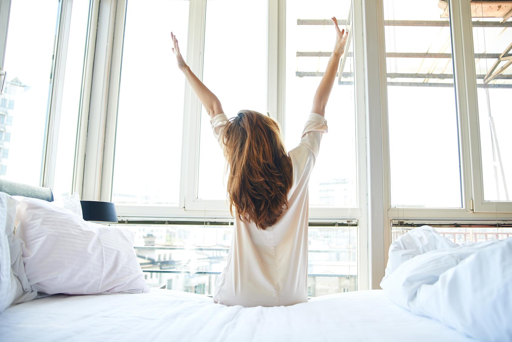 Frau wacht auf am Morgen vor Fenster
