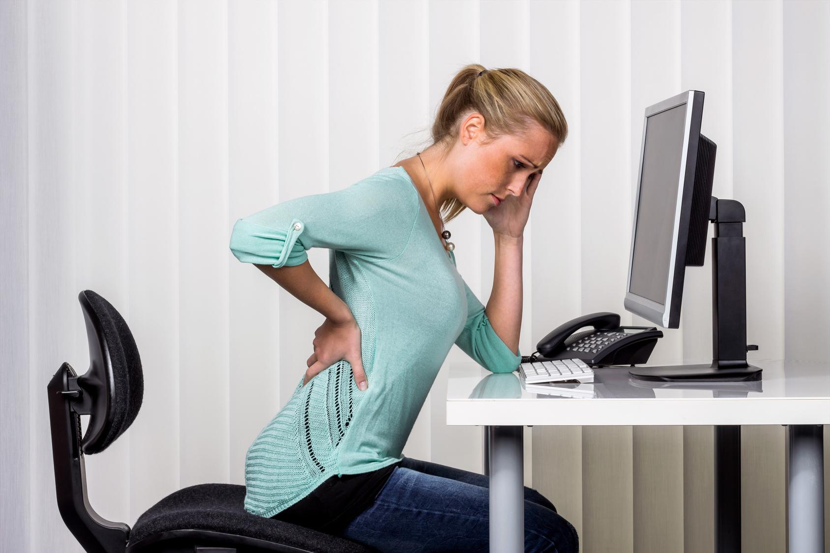 Frau mit Rückenschmerzen im Büro am Schreibtisch