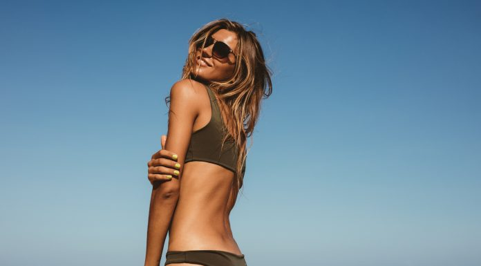 Frau im Bikini am Strand mit Sonnenbrille