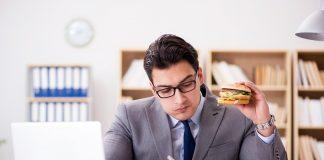 Geschäftsmann isst am Schreibtisch einen Burger