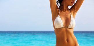 Frau post in weißem Bikini am Strand