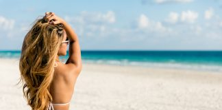 Frau am Strand im weißen Bikini