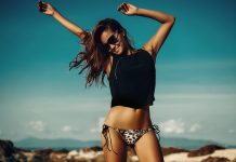 Frau tanzt am Strand im Bikini