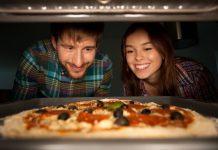 Pärchen wartet gespannt bis die Pizza im Ofen fertig wird