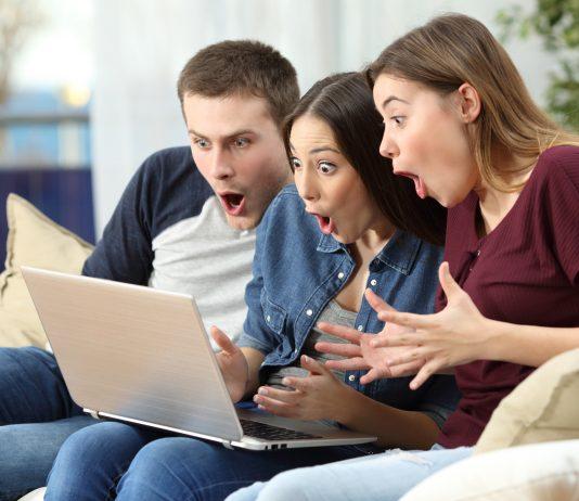 Drei Freunde sitzen vor dem Computer und freuen sich über ein Ergebnis