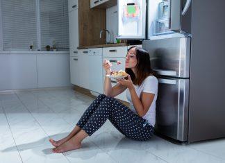 Heißhunger, Frau isst Süßigkeiten spät nachts vor dem Kühlschrank