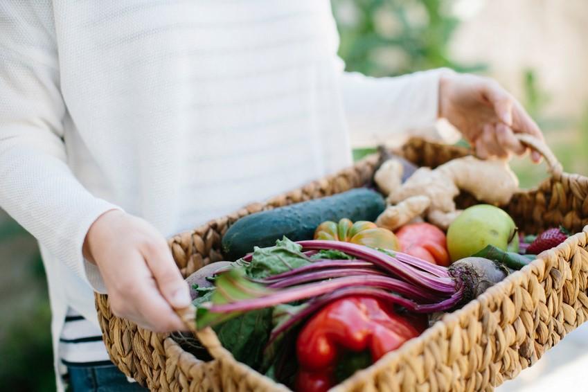 Frau trägt Korb mit Gemüse