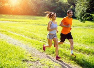 Mann und Frau joggen bei Sonnenuntergang im Park