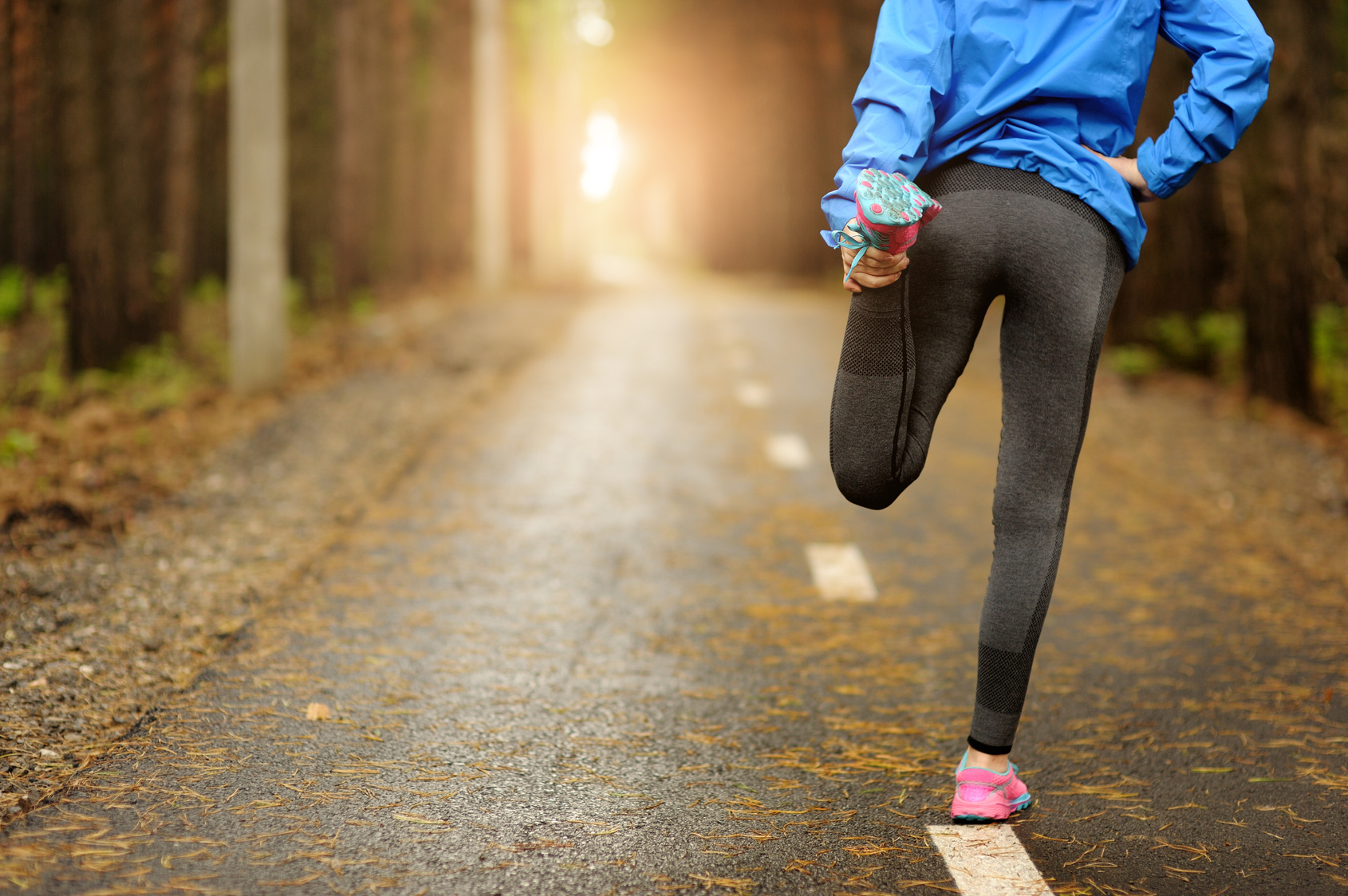 Frau dehnt sich vor dem Sport um fit durch den Herbst zu kommen