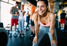 Frau im Fitnessstudio grinsend nach dem Training