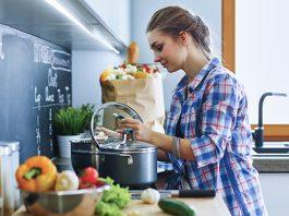 Frau steht am Ofen und kocht Low Carb