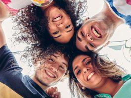 Vier Freunde umarmen sich freudig