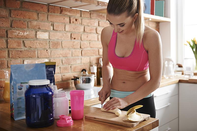 Frau bereitet einen Proteinsmoothie zu als Nahrungsergänzung