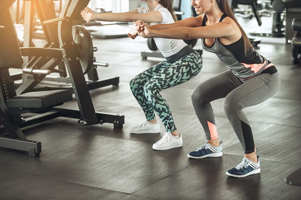 Zwei Frauen machen Squats im Fitnessstudio
