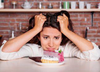 Frustessen, Frau sieht gequält auf ein Stück Kuchen und Schokolade, während sie sich durch die Haare fährt