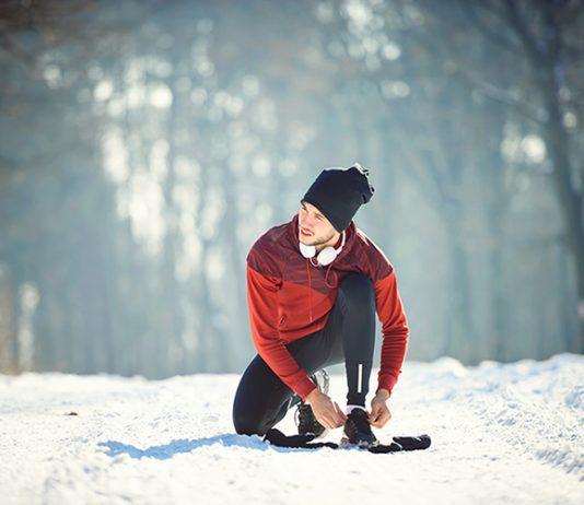 Fit durch den Winter - Mann bindet sich die Schuhe während Joggingpause