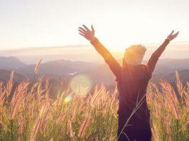 Frau bei Sonnenaufgang in den Bergen