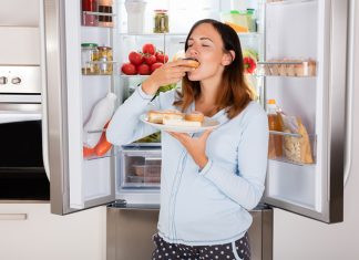 Frau hat Heißhunger auf Süßes und isst Süßigkeiten vor dem Kühlschrank