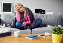 Frau sitzt mit Erkältung auf der Couch