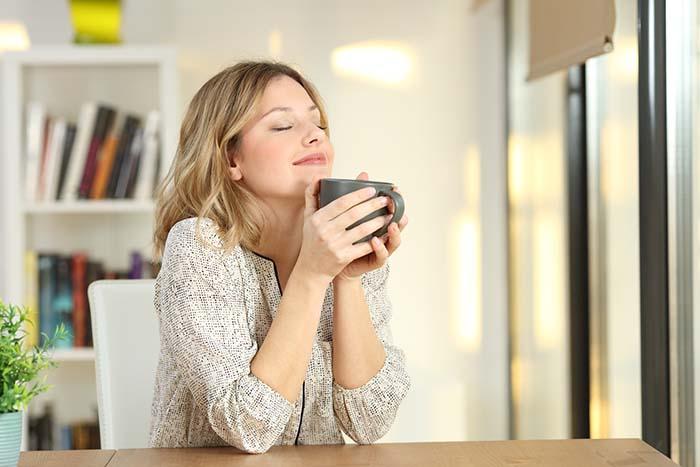 Frau trinkt entspannt ihren Kaffee am Morgen zuhause am Küchentisch