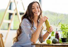 Frau trinkt einen grünen gesunden Shake in der Küche
