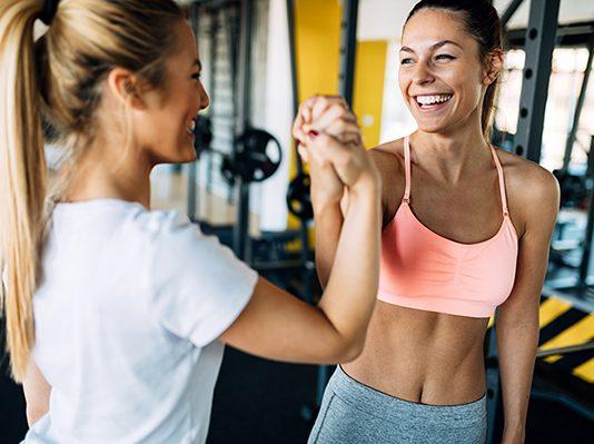 Zwei Frauen motivieren sich gegenseitig im Fitnessstudio