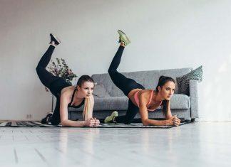 Zwei Freundinnen machen gemeinsam Po-Training zuhause im Wohnzimmer