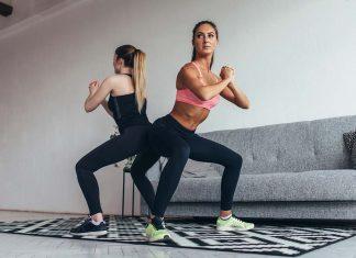 Zwei Freundinnen machen Squats zuhause im Wohnzimmer