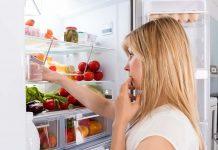 Frau hat ständig Hunger und sucht im Kühlschrank nach Essbarem