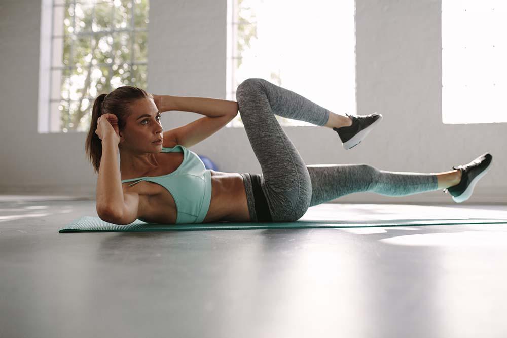 Frau macht Bauchmuskeltraining zuhause auf einer Trainingsmatte