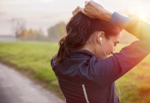 Frau macht sich einen Pferdeschwanz als Sportfrisur vor dem Training